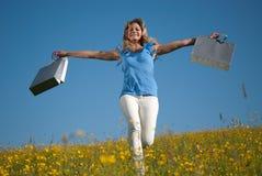 Junge Frau mit den Einkaufstaschen, die in eine Wiese springen Stockbilder