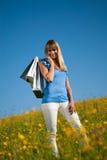 Junge Frau mit den Einkaufstaschen, die in einer Wiese stehen Stockbild