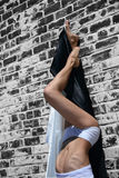 Junge Frau mit den Fahrwerkbeinen hob an und lehnte sich auf einer Wand Stockfoto