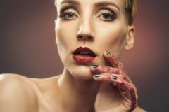 Junge Frau mit den gefunkelten Händen und den Lippen Stockfoto