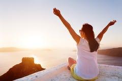 Junge Frau mit den Händen herauf bewundern Ansicht über Santorini, Griechenland Stockfotografie
