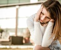 Junge Frau mit den Kopfschmerzen im Freien stockfotos