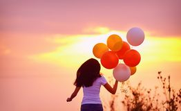 Junge Frau mit den Luftballonen, die Sommerfeld, auf Sonnenuntergang laufen lassen stockbild