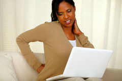 Junge Frau mit den rückseitigen Schmerz, die an Laptop arbeiten Stockbilder