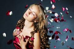 Junge Frau mit den rosafarbenen Blumenblumenblättern Stockfoto