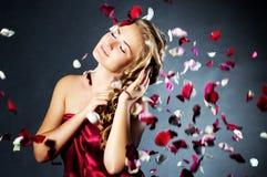 Junge Frau mit den rosafarbenen Blumenblumenblättern Stockbild