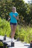 Junge Frau mit den Sommerkurzen hosen, die draußen in Naturpark laufen Lizenzfreies Stockfoto