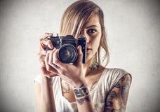 Junge Frau mit den Tätowierungen, die eine Kamera halten Lizenzfreie Stockfotografie