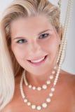 Junge Frau mit den weißen Zähnen und den Perlen Stockfoto