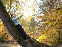 Junge Frau mit den Zöpfen stehend auf einem Baum und fotografiert gegen Lizenzfreie Stockfotografie