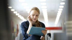 Junge Frau mit der Auflage, die im Warteraum sitzt stock video