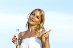Junge Frau mit der Flasche, die OKAYzeichen zeigt Stockfotografie