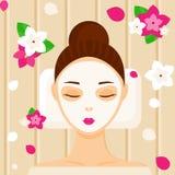 Junge Frau mit der Gesichtsmaske, die im Badekurortschönheitssalon sich entspannt Stockfoto