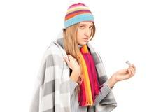Junge Frau mit der Grippe, die einen Thermometer anhält Stockfotos