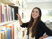 Junge Frau mit der Hand auf Buch und Hüfte Stockbilder