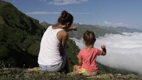 Junge Frau mit der kleinen netten Tochter, die auf den Berg sitzt stock video footage