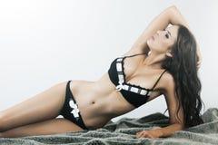 Junge Frau mit der sexy Karosserie, die in der Wäsche liegt Stockfotos