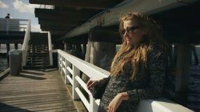 Junge Frau mit der Sonnenbrille, die auf Pier durch das Meer steht stock video footage