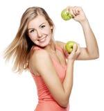 Junge Frau mit einem Apfel, der in Richtung Kameraisolators blickt lizenzfreie stockbilder