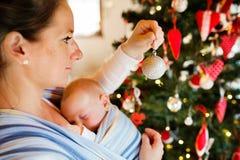 Junge Frau mit einem Baby, das Weihnachtsbaum verziert Stockfotografie