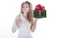 Junge Frau mit einem Champagner und Geschenk für Chris Stockfotografie