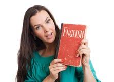 Junge Frau mit einem englischen Lehrbuch lizenzfreie stockfotos