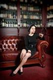 Junge Frau mit einem Glas Weinbrand Stockbild