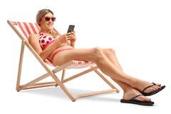 Junge Frau mit einem Handy in einem Klappstuhl Lizenzfreie Stockbilder