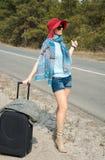 Junge Frau mit einem Koffer fährt auf dem Straßenzeigen per Anhalter Stockfotos