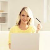 Junge Frau mit einem Laptop, der eine Kreditkarte hält Stockfotos