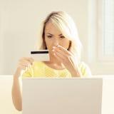Junge Frau mit einem Laptop, der eine Kreditkarte hält Lizenzfreie Stockfotos