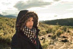 Junge Frau mit einem Mantel und einer Haube an stockbilder