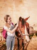 Junge Frau mit einem Pferd auf einer Ranch lizenzfreie stockbilder