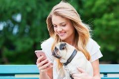 Junge Frau mit einem Pug behandelt ein Telefon lizenzfreie stockbilder