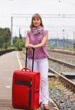 Junge Frau mit einem roten Koffer Stockbild