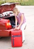 Junge Frau mit einem roten Koffer im Auto Stockfotografie