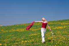 Junge Frau mit einem roten Schal auf einer Wiese Stockbild