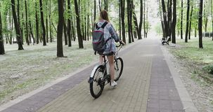 Junge Frau mit einem Rucksack fährt in den Park rad stock video footage