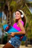 Junge Frau mit einem Skateboard lizenzfreies stockbild