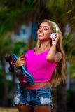 Junge Frau mit einem Skateboard stockfotos