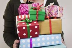 Junge Frau mit einem Stapel von Geschenken Lizenzfreie Stockbilder