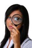 Junge Frau mit einem Vergrößerungsglasfrontseitengesicht Stockfotos