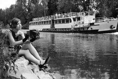 Junge Frau mit einer alten Kamera nahe dem Fluss Stockbilder