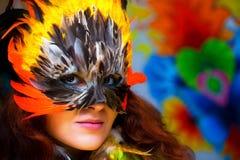 Junge Frau mit einer bunten Federkarnevals-Gesichtsmaske auf hellem buntem Hintergrund, Blickkontakt, bilden Künstler Lizenzfreie Stockfotografie