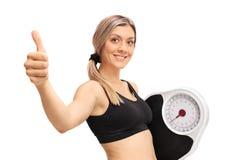 Junge Frau mit einer Gewichtsskala, die Daumen herauf Geste herstellt Stockfotos