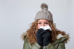 Junge Frau mit einer Kälte, die ihre Nase durchbrennt lizenzfreie stockfotografie