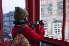 Junge Frau mit einer Kamera macht Fotos durch das Fenster Stockfotografie
