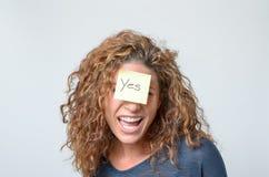 Junge Frau mit einer klebrigen Anmerkung in ihrem Gesicht Lizenzfreies Stockbild