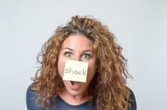 Junge Frau mit einer klebrigen Anmerkung in ihrem Gesicht Lizenzfreie Stockfotografie