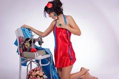 Junge Frau mit einer Nähmaschine kleidete im roten Neglige an Lizenzfreie Stockbilder